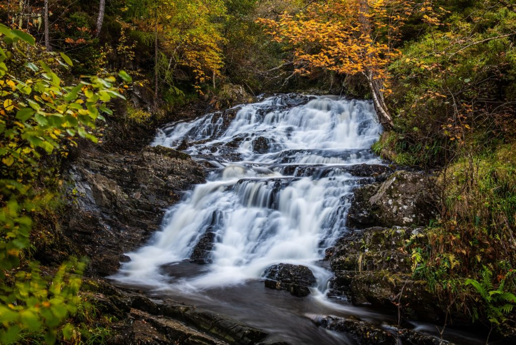 Small waterfalls on the Allt na Bodachan burn above the main drop at Plodda Falls in Glen Affric with the autumn colours in the trees