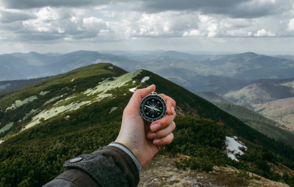 person holding compass on a mountain side