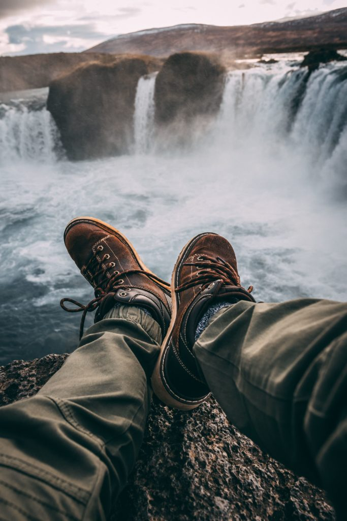 person sitting on rock near waterfalls