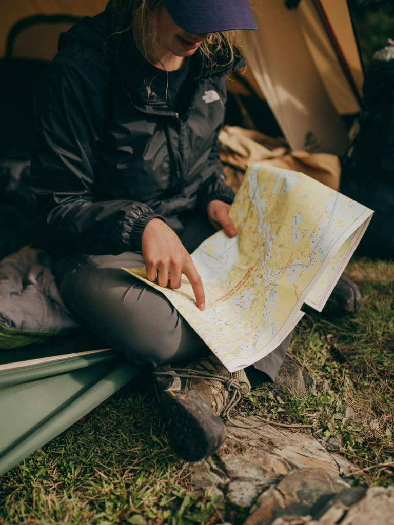photo of woman sitting while pointing on world map